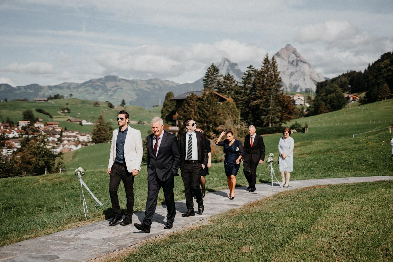 Hochzeitsfotograf in der Marienkapelle in Morschach Schweiz Hochzeitsfotografin kirchliche Trauung Schweizer Berge Alpen natürliche Hochzeitsfotografie Gäste laufen zur Kirche