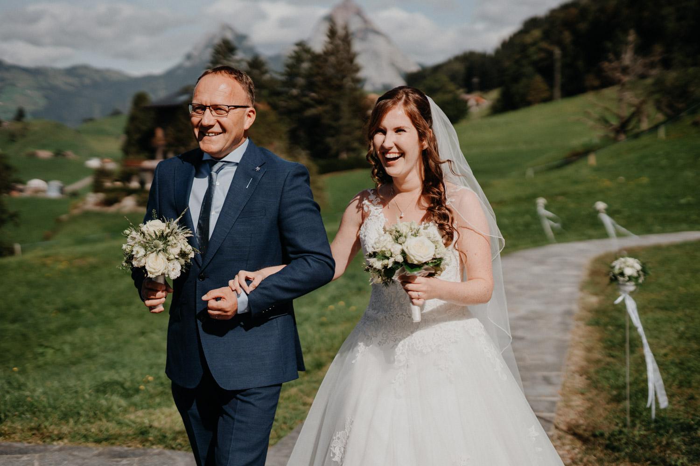 Hochzeitsfotograf in der Marienkapelle in Morschach Schweiz Hochzeitsfotografin kirchliche Trauung Schweizer Berge Alpen natürliche Hochzeitsfotografie Braut Brautvater Einzug