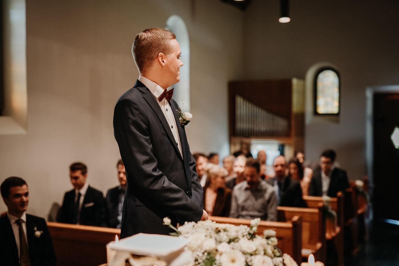 Hochzeitsfotograf in der Marienkapelle in Morschach Schweiz Hochzeitsfotografin kirchliche Trauung Schweizer Berge Alpen natürliche Hochzeitsfotografie Bräutigam wartet auf Braut