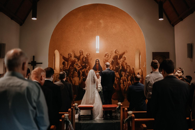 Hochzeitsfotograf in der Marienkapelle in Morschach Schweiz Hochzeitsfotografin kirchliche Trauung Schweizer Berge Alpen natürliche Hochzeitsfotografie Kuss kirchliche Trauung