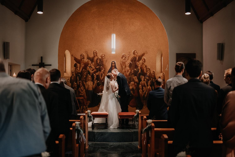 Hochzeitsfotograf in der Marienkapelle in Morschach Schweiz Hochzeitsfotografin kirchliche Trauung Schweizer Berge Alpen natürliche Hochzeitsfotografie Kuss