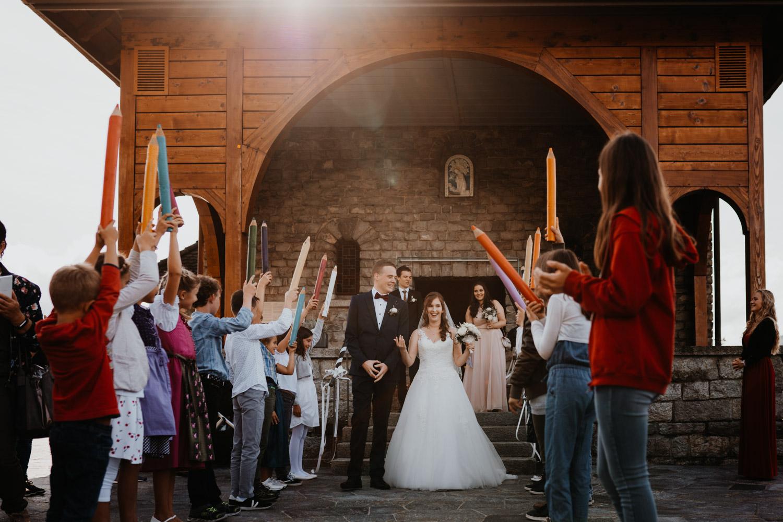Hochzeitsfotograf in der Marienkapelle in Morschach Schweiz Hochzeitsfotografin kirchliche Trauung Schweizer Berge Alpen natürliche Hochzeitsfotografie Auszug Brautpaar Spalier