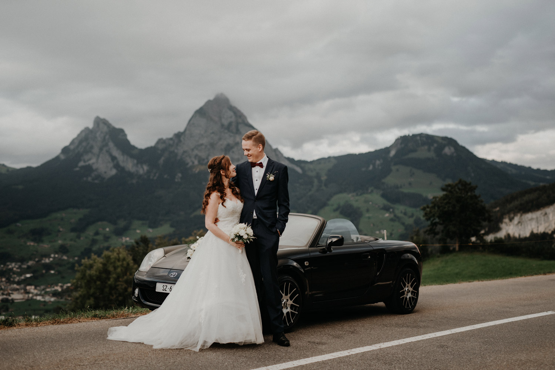 Hochzeitsfotograf in der Marienkapelle in Morschach Schweiz Hochzeitsfotografin kirchliche Trauung Schweizer Berge Alpen natürliche Hochzeitsfotografie Brautpaarshooting in den Bergen natürliche ungestellte Hochzeitsreportage Cabriolet Auto