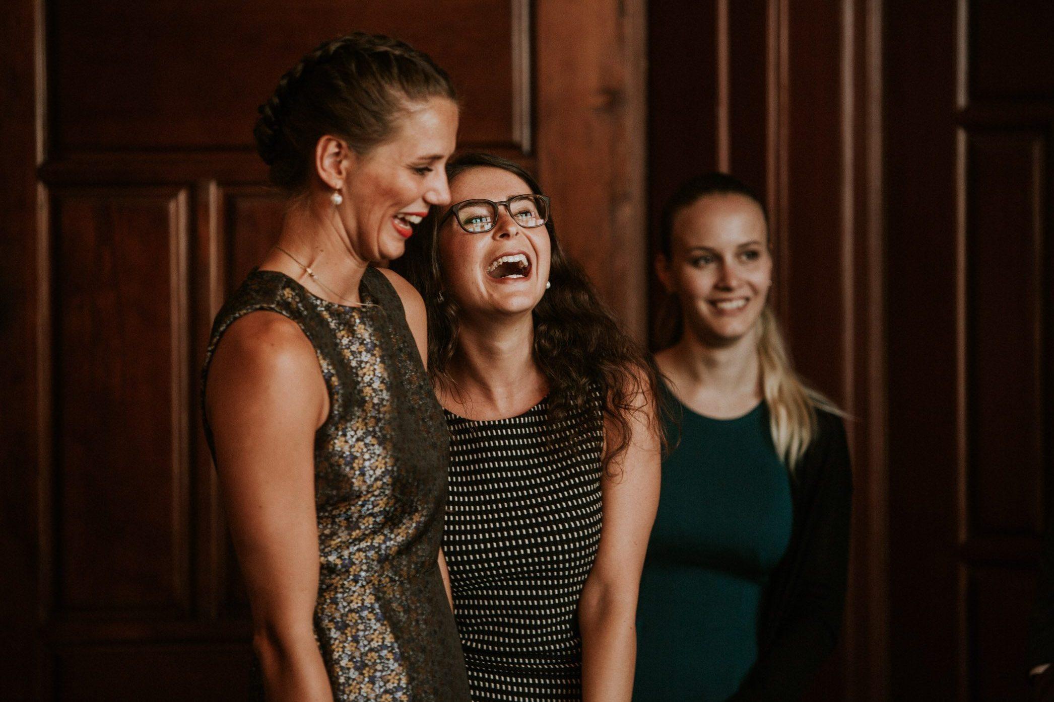 Braut und Freundin lachen bei einer standesamtlichen Trauung im Zivilstandesamt Zürich