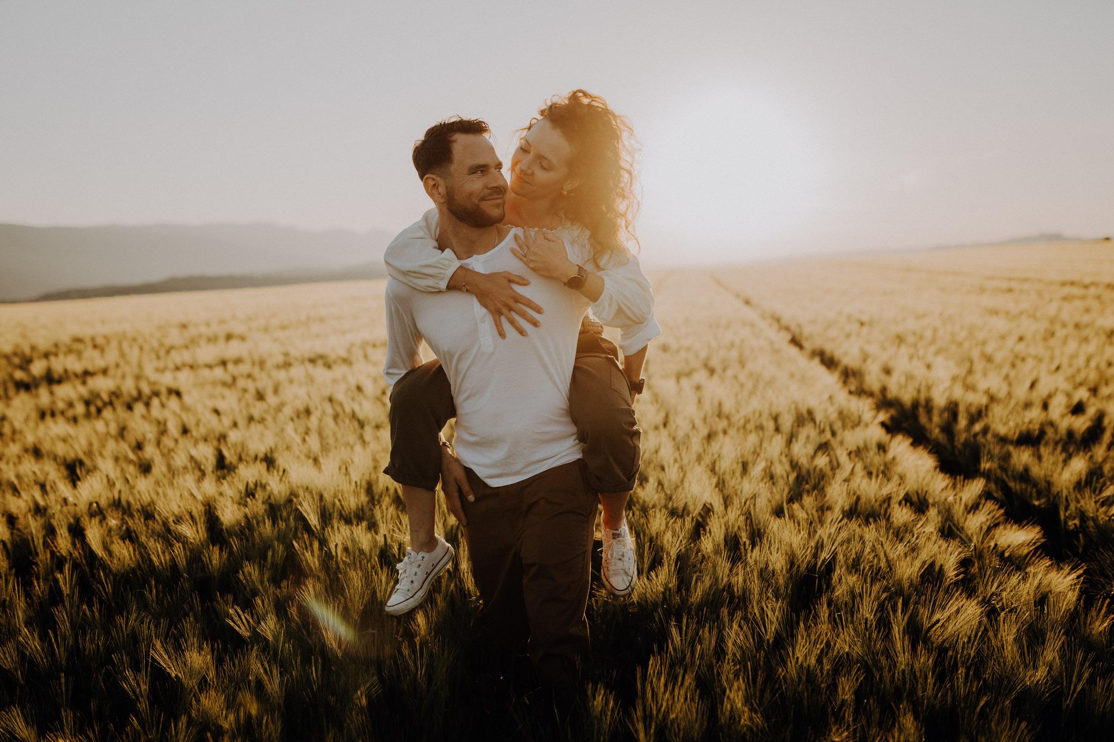 Verlobungsshooting in Bern Paarshooting natürlich ungestellt Schweiz Hochzeitsfotografin Weizenfeld Gegenlicht authentisch keine Posen Huckepack