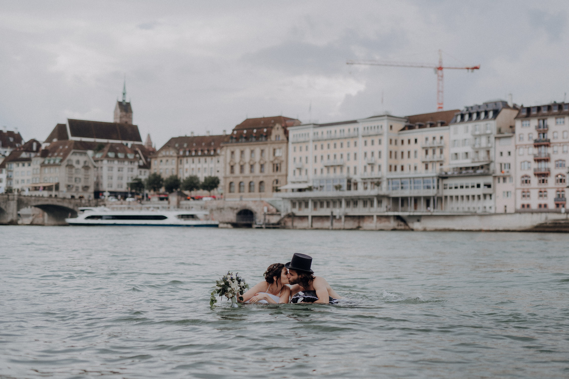 Wedding photographer switzerland basel natural unposed civil wedding old town Basel Minster couple shoot bohemian style documentary rainy wedding bride and groom swimming in the river rhine